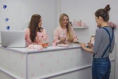 Jovens mulheres o contador da recepção Foto de Stock