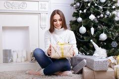 Jovens mulheres que abrem um presente de Natal em uma manhã de Natal Foto de Stock