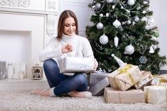 Jovens mulheres que abrem um presente de Natal em uma manhã de Natal Imagem de Stock