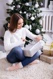 Jovens mulheres que abrem um presente de Natal em uma manhã de Natal Fotos de Stock
