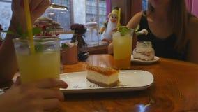 Jovens mulheres que bebem a limonada e que comem bolos no café vídeos de arquivo