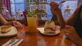 Jovens mulheres que bebem a limonada e que comem bolos no caf? filme