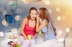 Jovens mulheres que bebem o chá e que bisbilhotam em casa Imagem de Stock