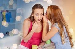 Jovens mulheres que bebem o chá e que bisbilhotam em casa Imagens de Stock Royalty Free