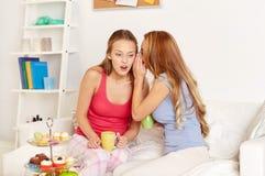 Jovens mulheres que bebem o chá e que bisbilhotam em casa Fotografia de Stock Royalty Free
