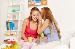 Jovens mulheres que bebem o chá e que bisbilhotam em casa Fotos de Stock Royalty Free