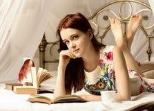Jovens mulheres que bebem o chá e que leem um livro em uma cama em casa Fotografia de Stock