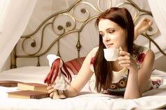 Jovens mulheres que bebem o chá e que leem um livro em uma cama em casa Imagem de Stock