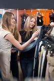 Jovens mulheres que compram calças de brim fotografia de stock royalty free