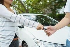 Jovens mulheres que dão um carro chave ao homem novo na fonte de carro foto de stock