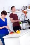 Mulher que desbasta os vegetais e o homem que lançam o alimento na bandeja fotos de stock royalty free
