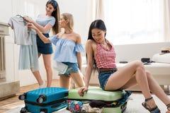 Jovens mulheres que embalam malas de viagem para férias junto em casa Fotos de Stock Royalty Free
