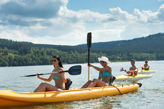 Estudantes novos que kayaking na luz do sol fotos de stock
