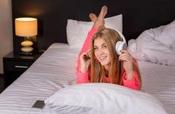 Jovens mulheres que escutam a música do smartphone na cama foto de stock