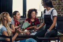Jovens mulheres que estudam junto com livros e dispositivos digitais dentro imagens de stock royalty free