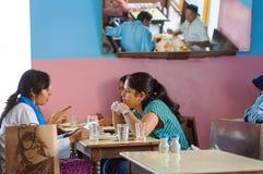 Jovens mulheres que falam e que têm o jantar no café indiano popular com interior colorido Fotografia de Stock Royalty Free