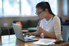 Jovens mulheres que fazem o trabalho em seu laptop em casa fotografia de stock
