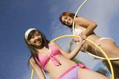 Jovens mulheres que guardaram a aro de Hula foto de stock