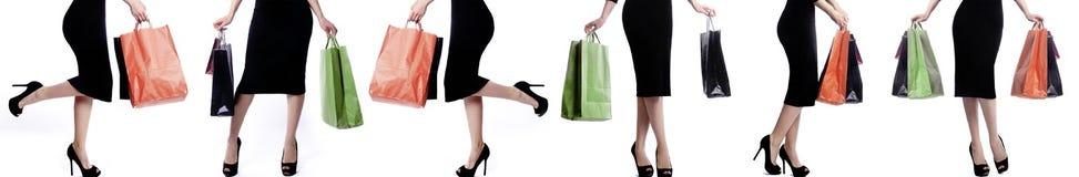 Jovens mulheres que mantêm sacos da loja isolados no fundo branco Pacotes da compra Papel de parede sem emenda dos pés fêmeas bon Fotos de Stock