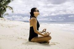 Jovens mulheres que meditam sobre a praia tropical pristine fotografia de stock royalty free