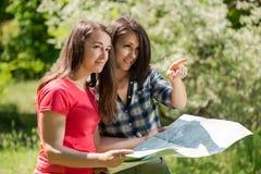 Jovens mulheres que olham o mapa durante o passeio na montanha fotografia de stock
