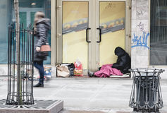 Jovens mulheres que passam a situação desabrigada do homem no tempo frio no fim imagens de stock royalty free