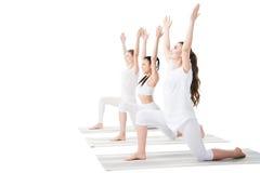 Jovens mulheres que praticam a postura de Anjaneyasana em esteiras da ioga imagens de stock