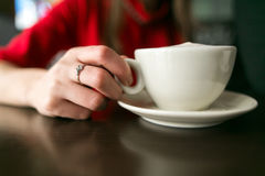 Jovens mulheres que sentam e que bebem o café no restaurante do café um copo com café está na tabela Mão da mulher Povos no amor imagens de stock
