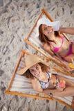 Jovens mulheres que sentam-se em cadeiras de plataforma ao rir junto imagem de stock