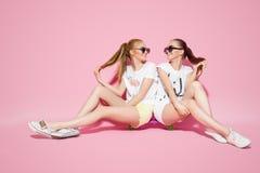 Jovens mulheres que sentam-se no skate fotografia de stock