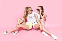 Jovens mulheres que sentam-se no skate imagem de stock