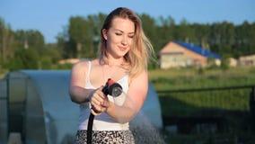 Jovens mulheres que sorriem molhando um jardim do verão video estoque