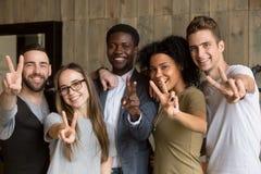 Jovens multi-étnicos felizes que mostram o sinal de paz que olha o Ca fotografia de stock royalty free