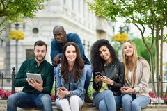 jovens Multi-étnicos que usam o smartphone e os tablet pc imagens de stock royalty free