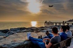 Jovens no por do sol de observação da praia Fotos de Stock Royalty Free