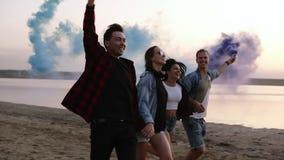Jovens quatro povos que correm com a granada de fumo colorido em suas mãos pelo mar durante o por do sol Divertimento, fumo color filme