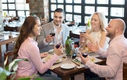 Jovens que apreciam o alimento na taberna Imagem de Stock