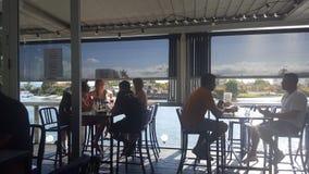Jovens que apreciam uma bebida antes do por do sol na barra do leme, surfistas Paradise, Queensland fotografia de stock royalty free