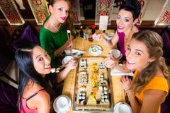 Jovens que comem o sushi no restaurante Foto de Stock Royalty Free