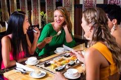Jovens que comem o sushi no restaurante imagens de stock