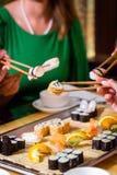 Jovens que comem o sushi no restaurante Fotografia de Stock Royalty Free