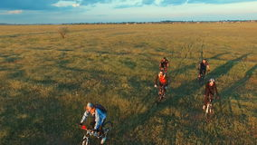 Jovens que dão um ciclo em bicicletas através do campo verde e amarelo do prado do verão vídeos de arquivo