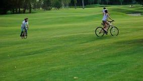 Jovens que dão um ciclo no gramado verde vídeos de arquivo