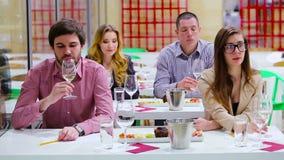 Jovens que degustating um vinho branco e comer petiscos filme