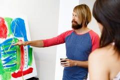 Jovens que estão em uma galeria e que contemplam a arte finala fotografia de stock
