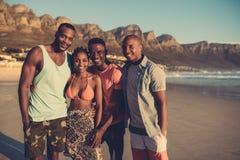Jovens que estão junto na praia Foto de Stock