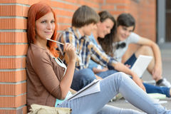 Jovens que estudam os amigos da mulher que sentam-se no fundo Foto de Stock Royalty Free