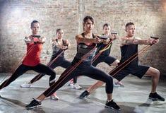 Jovens que fazem o exercício com faixa elástica imagem de stock royalty free