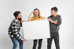 Jovens que guardam a placa branca fotografia de stock royalty free