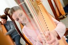 Jovens que jogam harpa imagens de stock royalty free